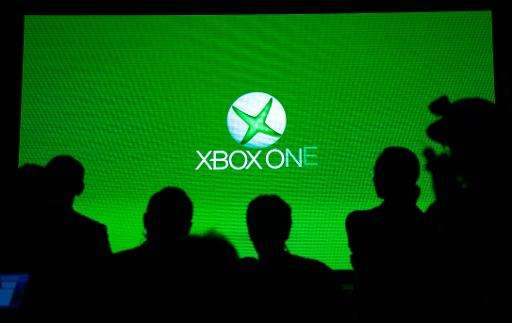People look at a screen during the presentation of the Xbox One in Shanghai, China, on July 30, 2014