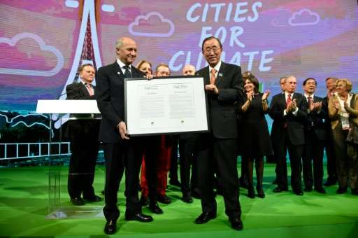 UN Secretary General Ban Ki-moon (R) and France's Foreign Minister Laurent Fabius (L) pose with the Paris City Hall Declaration