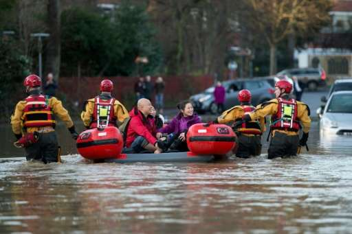 Members of the emergency services transport residents to safety after their homes were flooded in York, northern England, on Dec
