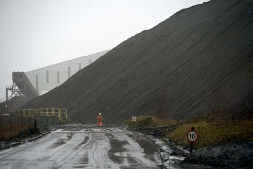 A mine worker walks past a slag heap at the entrance to Kellingley Colliery, the last deep coal mine operating in Britain near K