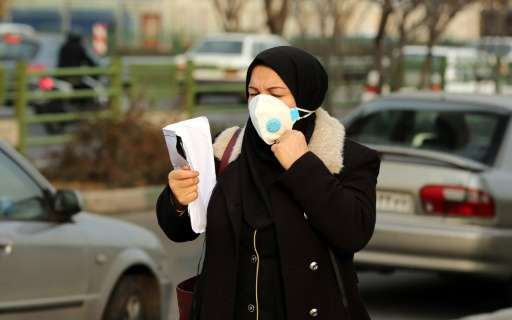 An Iranian woman wears a facemask as she walks in a heavily polluted area in Tehran on December 19, 2015 as the capital city's a