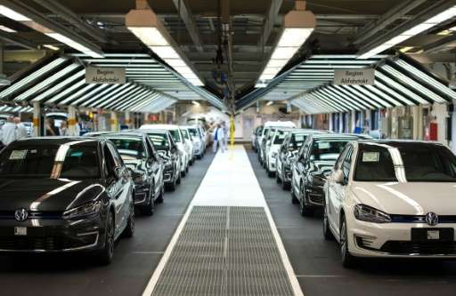 Employees of German car maker Volkswagen check cars at a assembly line of the VW plant in Wolfsburg, central Germany, on October