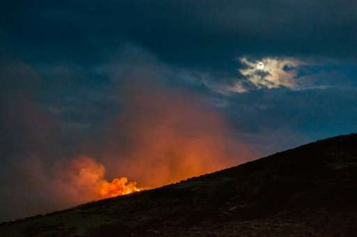 Flames and smoke columns, due to wildfires, raise in La Roza rural area, near Cangas de Onis, where a helicopter that was battli