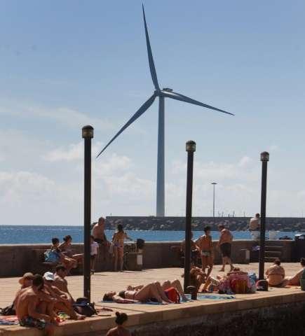 People sunbathe near Spain's largest wind turbine, a 154 m tall 5 mw installation in Arinaga port on Gran Canaria