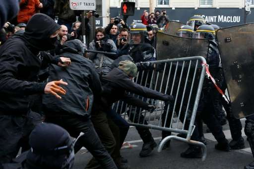 Protestors clash with riot police during a rally against global warming in Paris, a day ahead of the start of the UN conference