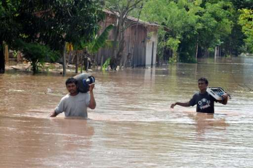 Residents of El Progreso in Honduras leave their flooded homes following Tropical Storm Matthew in 2010