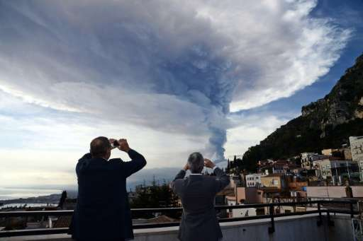 Smoke rises over the city of Taormina during an eruption of Mount Etna on December 4, 2015