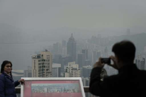 Tourists take pictures of haze over Hong Kong on January 9, 2014