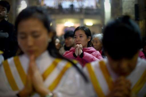 Worshippers attend the Christmas Eve mass at a Catholic church in Beijing on December 24, 2015