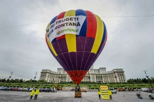 """Activists stand next to a hot air balloon with a banner reading """"Do not destroy Rosia Montana"""", to protest against the"""