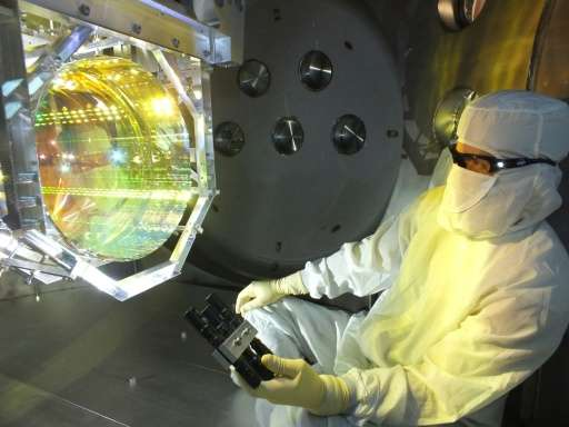 A Laser Interferometer Gravitational Wave Observatory optics technician inspects the equipment that will be used to conduct test