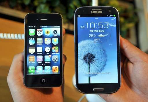 An Apple's iPhone 4s (L) and a Samsung's Galaxy S3 are displayed at a mobile phone shop in Seoul on August 27, 2012