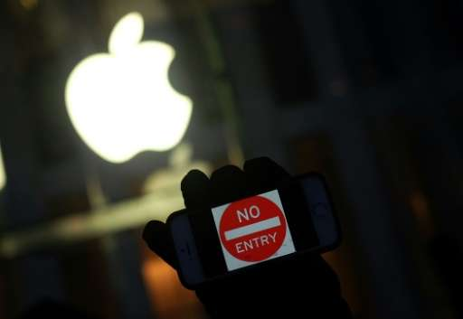 """A protester holds up his iPhone with a sign """"No Entry"""" during a demonstration in New York on February 23, 2016, Apple"""