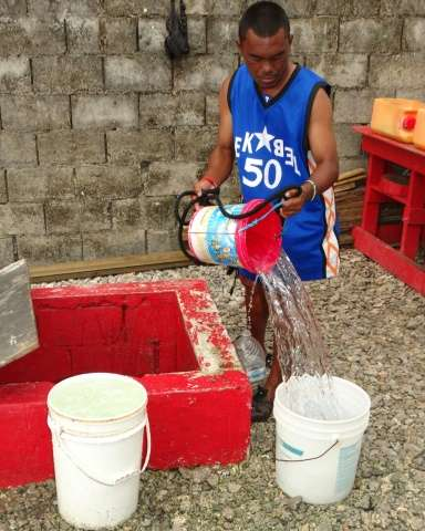 A resident fills buckets from a well in Majuro, Marshall Islands