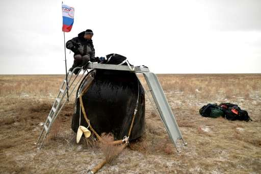 A search and rescue team secures the Soyuz TMA-18M space capsule carrying International Space Station crew US astronaut Scott Ke