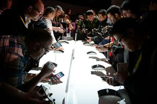 Attendees check out LG G Flex2 smart phones, during the 2015 Consumer Electronics Show in Las Vegas, Nevada