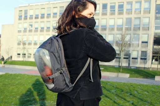"""A woman wears """"The Plant Bag"""", a backpack fitted with a breathing mask connected to the pack which contains a plant on"""