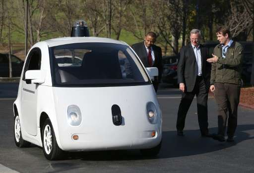 Google's Chris Urmson (R) shows a Google self-driving car to U.S. Transportation Secretary Anthony Foxx (L) and Google Chairman
