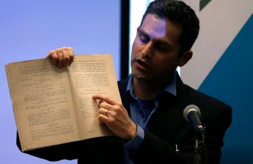 Israeli Professor Barak Kol, head of the physics department at the Hebrew University of Jerusalem, shows the original document w