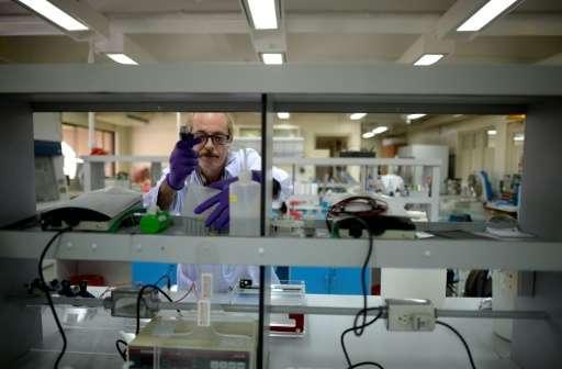 Kenneth McNally, a US biochemist at the Philippines-based International Rice Research Institute (IRRI), checks laboratory equipm