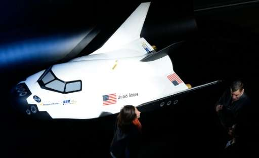 People stand next to a model of a new space shuttle designed by US company Sierra Nevada Corporation (SNC)