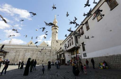 Syrians watch pigeons flying outside the Umayyad Mosque in the Syrian capital, Damascus, on November 10, 2015