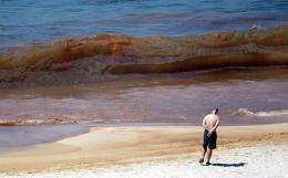 A beachgoer looks at oil in the water on Orange Beach, Alabama in June