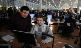 A blind trainee at a hi-tech call centre gets instructions from a supervisor