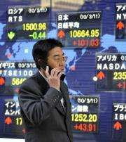 A businessman uses his mobile phone while passing a share prices board in Tokyo