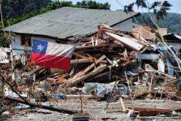 A Chilean flag flutters next to a destroyed house in Constitucion