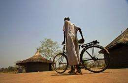 A displaced Sudanese man pushes his bike through Malou village in southern Sudan's Lakes State