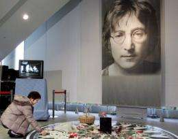 A Japanese woman offers a flower before a large portrait of John Lennon