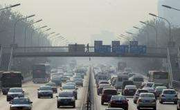 A pedestrian walks across an overpass above traffic on a hazy day in Beijing
