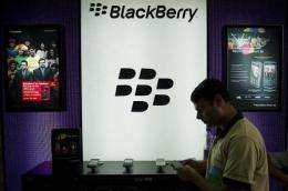 A salesman stands next to a BlackBerry display in a shop