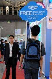 A Skype promoter walks with a sign at the CommunicAsia 2010 conference