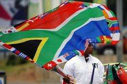 A street vendor selling flags waves a South African national flag decorated with those of the countries participating
