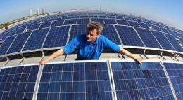 A technician checks the panels of a solar power system