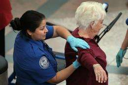 A traveler undergoes an enhanced pat down by a TSA agent