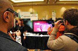 Attendees watch 3D entertainment at the Sensio media display