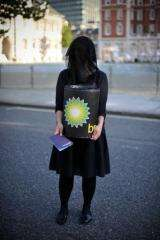 A woman carries a 'BP oil barrel' during a protest by artists calling themselves 'The Good Crude Britannia'