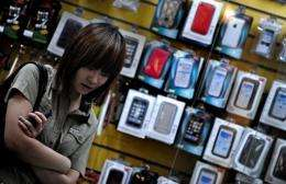 A woman stands in front of a shop selling mobile phone accessories in Shanghai