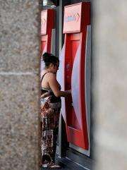 A woman uses an Automated Teller Machine (ATM)