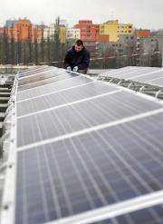 A worker adjusts the solar panels on the roof of the Max-Schmeling-Halle in Berlin