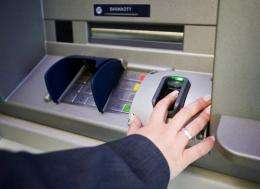 A worker of Polish Bank BPS shows how to withdraw money from a new cash machine