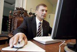 Estonian Prime Minister Andrus Ansip tries out Internet voting in Tallinn as he casts his ballot from his office in 2005