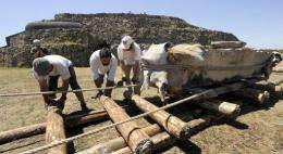 French archaeologist Cyril Chaigneau (2ndL) sets wooden logs before moving a stony block weighing 4.2 tonnes