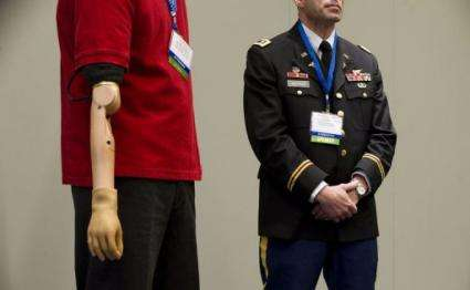 Glen Lehman (L), a retired sergeant first class in the United States Army stands with his bionic arm