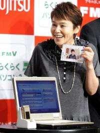 Japanese actress Shinobu Otake displays a notebook PC for senior citizens