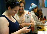 Local resident Susan Linsky (2nd L) watches as her daughter Arielle (L) tries out the Palm Pre smartphone