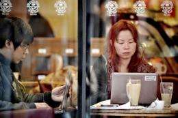 People surf the Internet on their laptops at a wifi cafe in Shanghai